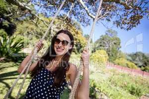 Smiling woman sitting on swing in park