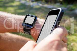 Man hands wearing smart watch and using mobile phone