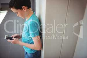 Schoolboy using mobile phone in corridor at school