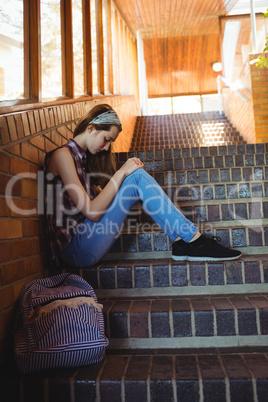 Sad schoolgirl sitting alone on staircase