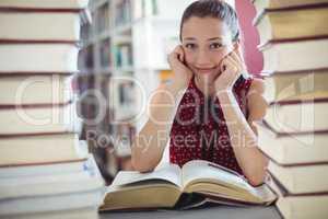 Portrait of happy schoolgirl studying library