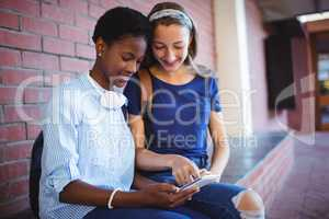 Schoolgirls sitting against brick wall and using mobile phone