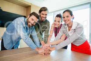 Business executives with their hands stacked on wooden table at office