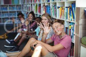 Students sitting in library and waving hands