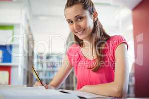 Schoolgirl doing homework in in library at school