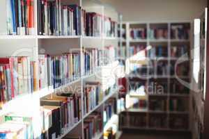 Various books arranged in bookshelf in library
