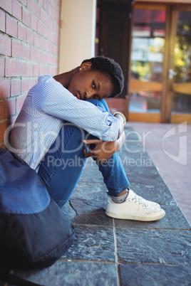 Portrait of sad schoolgirl sitting against brick wall