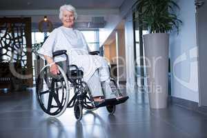 Disabled senior patient on wheelchair in hospital corridor