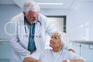 Doctor holding senior patient on wheelchair in passageway