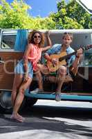 Man playing guitar in campervan and woman standing beside him