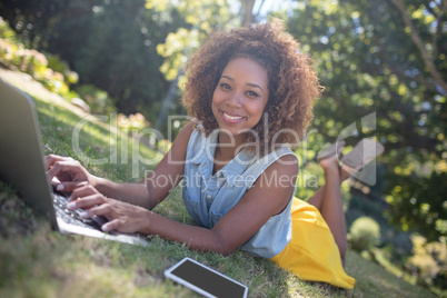 Smiling woman lying on grass and using laptop