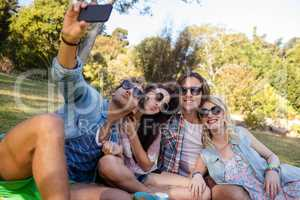 Friends clicking selfie while having picnic
