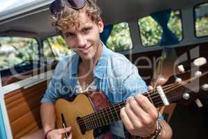 Man playing guitar in campervan