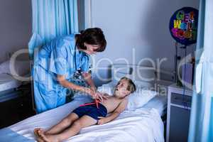 Female doctor examining abdomen of patient