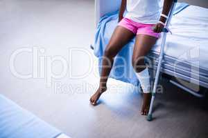 Girl with crutches sitting on hospital bed in ward