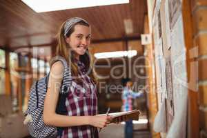 Portrait of smiling schoolgirl standing with book near notice board in corridor