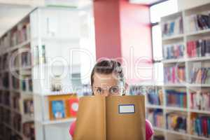 Portrait of schoolgirl hiding her face with book in library
