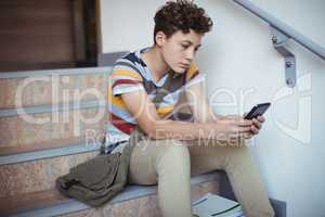 Attentive schoolboy sitting on staircase and using mobile phone