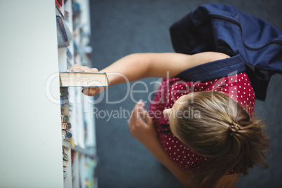 High angle view of schoolgirl selecting book from bookshelf in library
