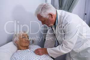 Doctor examining senior patient with stethoscope