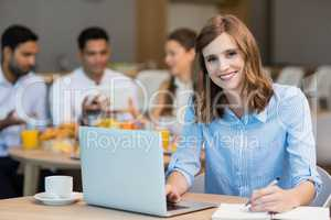 Smiling businesswoman working on laptop while having coffee in office cafeteria