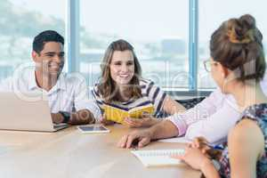 Smiling business colleagues interacting with each other in meeting