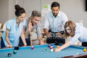 Business executive taking picture with mobile phone while colleagues playing pool