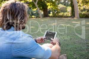 Man sitting on grass using digital tablet