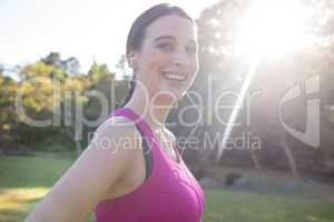 Portrait of smiling female jogger listening to music