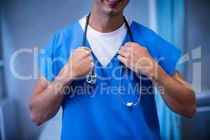 Close-up of male doctor standing with stethoscope in ward