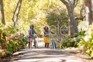 Happy couple walking with bicycle