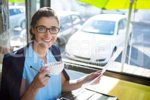 Female executive looking at document while having coffee