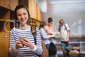 Portrait of happy schoolgirl holding mobile phone in locker room