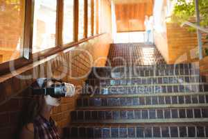 Schoolgirl using virtual reality headset on staircase