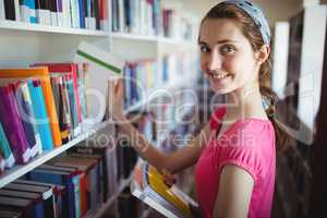 Schoolgirl selecting book from book shelf in library at school