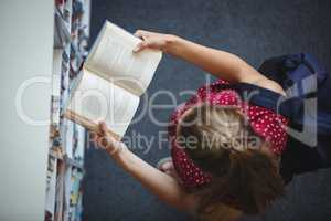 High angle view of attentive schoolgirl reading book in library