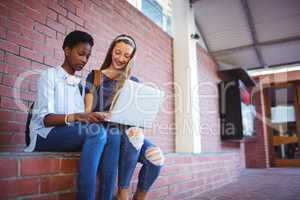 Schoolgirls sitting against brick wall and using laptop