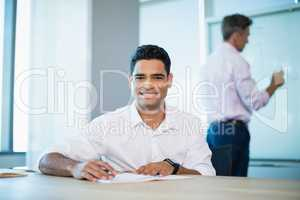 Portrait of smiling business executive writing on notebook in conference room