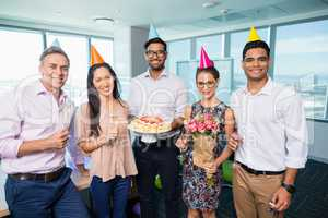 Portrait of smiling business colleagues celebrating birthday