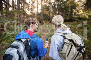 Rear view of hiking couple holding a compass and pointing forward