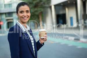 Business executive holding disposable coffee cup