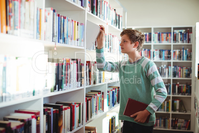 Schoolboy selecting book in library