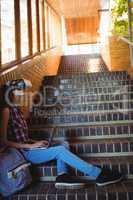 Schoolgirl using virtual reality headset and laptop on staircase