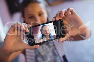 Schoolgirl taking selfie on mobile phone