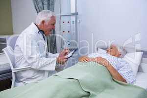 Doctor discussing report with senior patient in ward