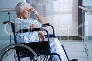 Disabled senior patient on wheelchair in hospital passageway
