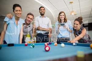 Smiling business colleagues playing pool in office space