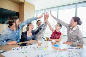 Team of business executives giving high five in conference room