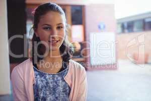 Happy schoolgirl sitting in school campus