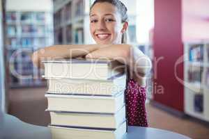 Portrait of happy schoolgirl leaning of stacked books in library